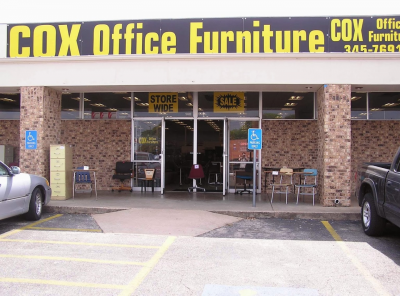 Shot from parking lot showing Cox Office Furniture storefront with sale signs